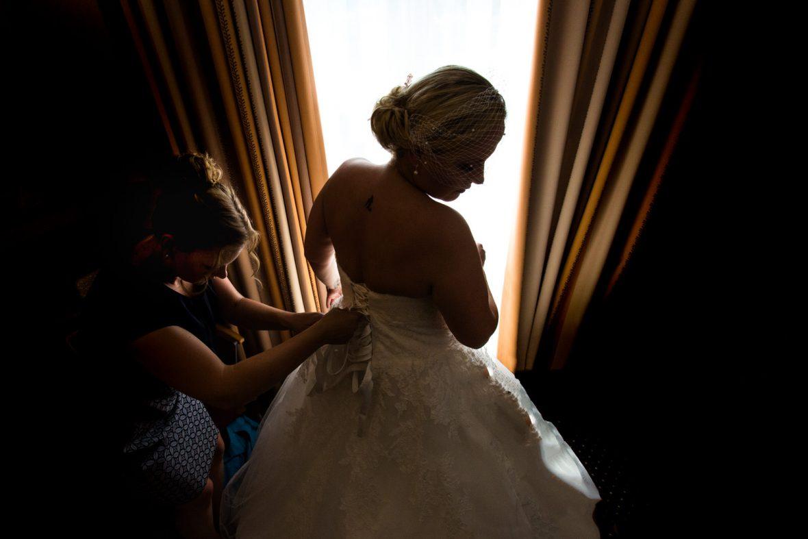Anziehen des Brautkleides bei einer Vintage-Hochzeit in der Zehntscheune in Hanau fotografiert von Hochzeitsfotograf Steven Herrschaft aus Wiesbaden