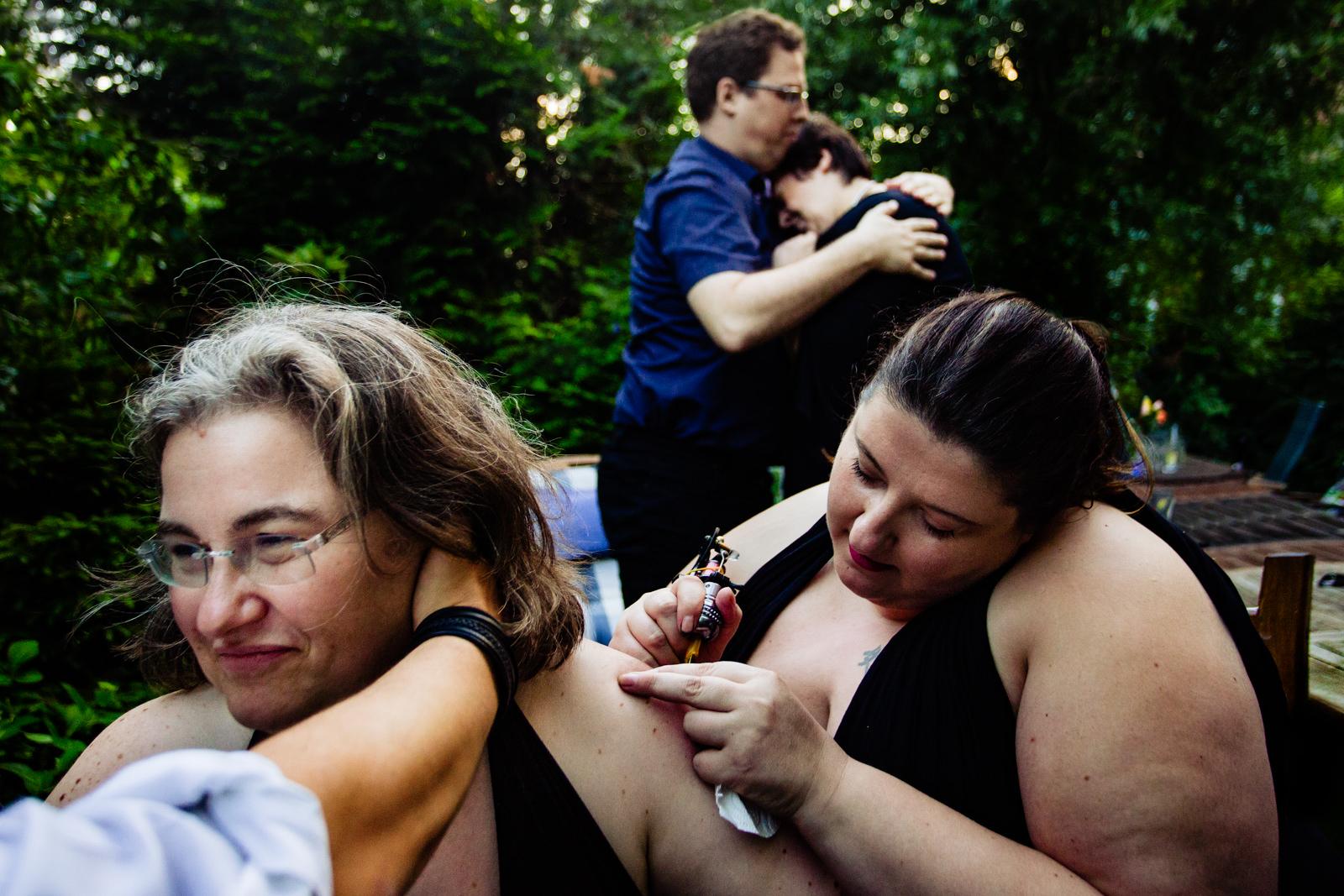 Hochzeitspaar wird tätowiert bei freier Trauung von Trautante Friederike Delong bei einer Gartenhochzeit in Hamburg fotografiert von Hochzeitsfotograf Steven Herrschaft aus Wiesbaden