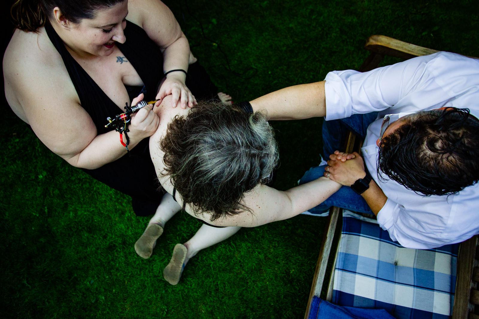 Braut wird tätowiert bei freier Trauung von Trautante Friederike Delong bei einer Gartenhochzeit in Hamburg fotografiert von Hochzeitsfotograf Steven Herrschaft aus Wiesbaden