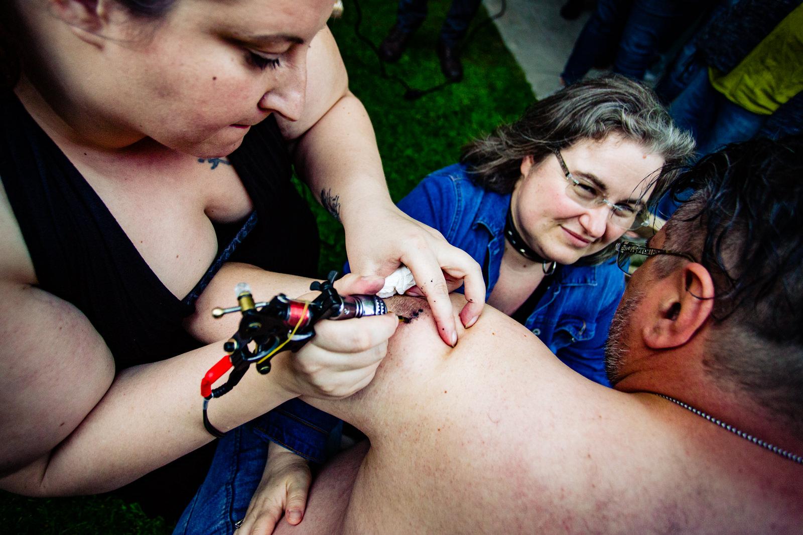 Tattoo stechen bei freier Trauung von Trautante Friederike Delong bei einer Gartenhochzeit in Hamburg fotografiert von Hochzeitsfotograf Steven Herrschaft aus Wiesbaden